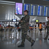 In Paris, soldiers patrol at Charles de Gaulle airport last week. French airports have reportedly agreed to a new TSA policy requiring electronic devices to be powered up before they're allowed on U.S.-bound flights.