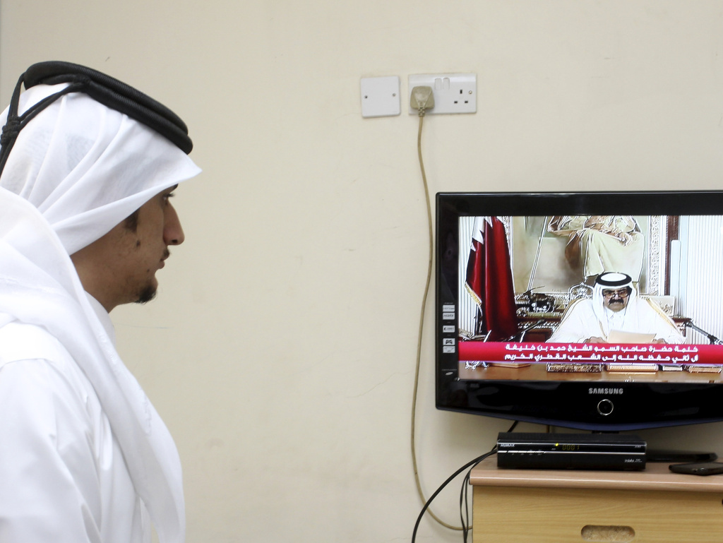 A man watches a televised address by Qatar's Emir Sheik Hamad bin Khalifa Al Thani, in Doha, Qatar, on Tuesday. Qatar's ruler transferred power to his 33-year-old son, making him the youngest leader in the region.