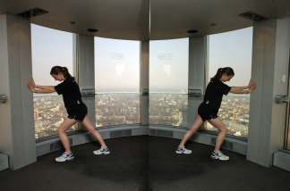 A competitor is reflected in a mirrored wall as she stretches after taking part in 'Vertical Rush' a race up the stairwell of Tower 42, the tallest building in the City of London.