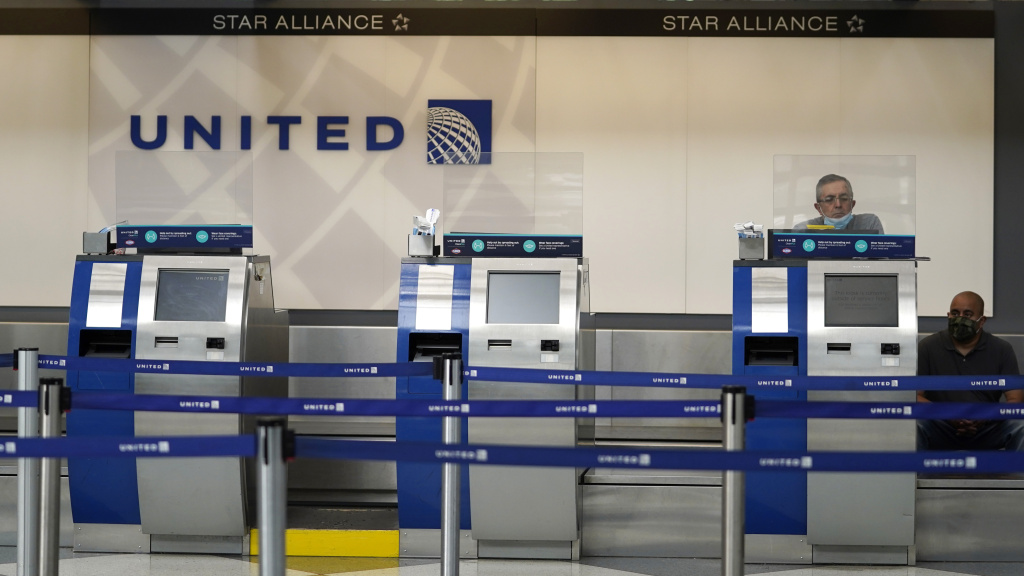 United Airlines employees work at ticket counters at Chicago's O'Hare International Airport on Oct. 14. United and other airline stocks have been hard-hit by the pandemic economic slowdown.