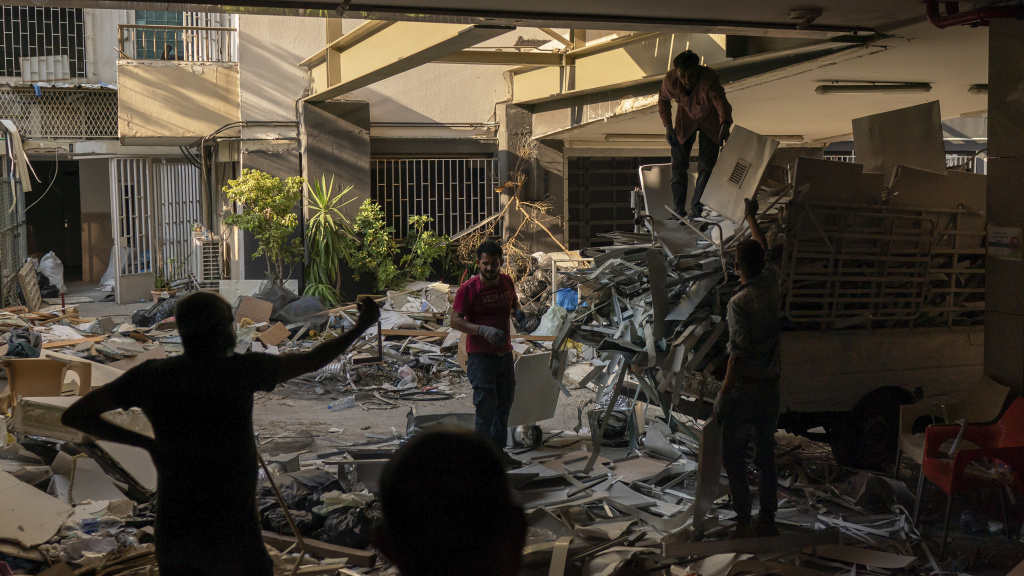 Workers remove debris from a hospital that was heavily damaged in last month's explosion in Beirut. Lebanon's interim health minister, Hamad Hasan, told local media last month that the health system was