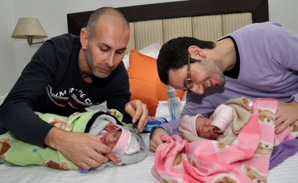 Spanish couple Mauro and Juan Carlos play with their new baby girls.