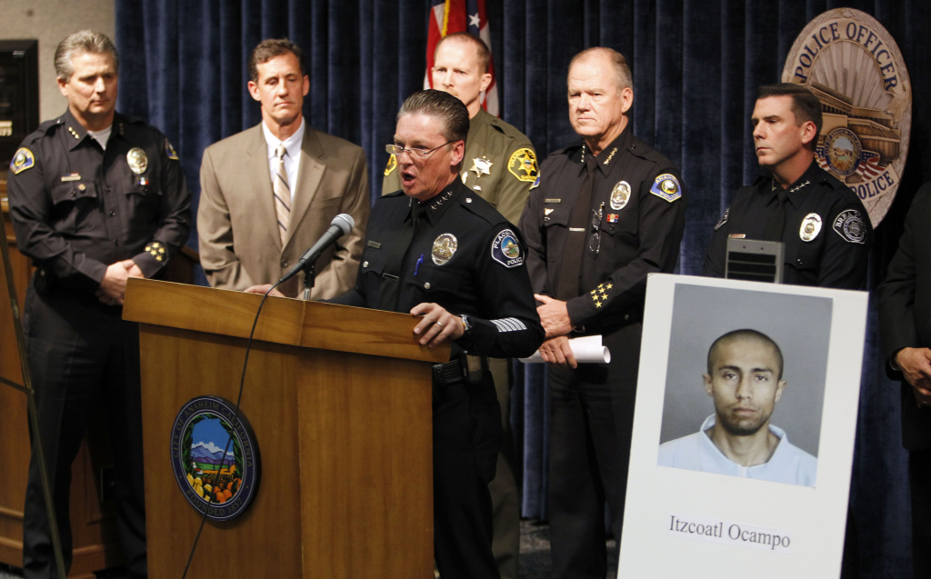 Placentia police chief Rick Hicks speaks at the podium before several police chiefs and an FBI special agent for a news conference to announce the arrest of Itzcoatl Ocampo as the serial killer of four homeless men, the latest Friday night, where Ocampo was caught in Anaheim, Calif., Saturday, Jan. 14, 2012.