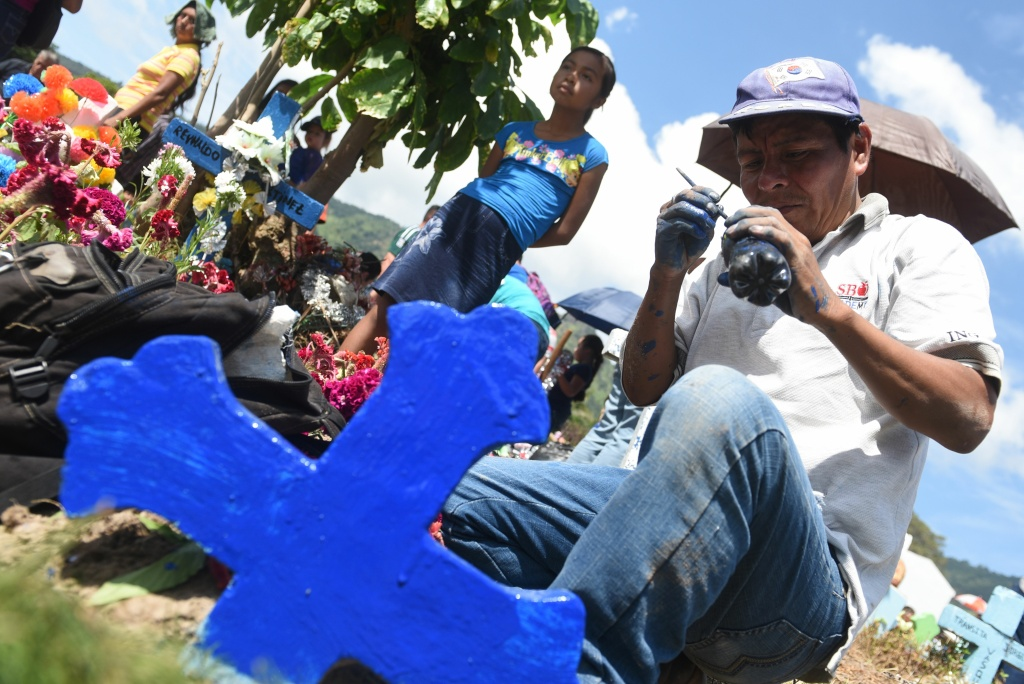 A man makes improvements to the grave of a loved one during the commemoration of the day of the dead at a cemetery in Panchimalco, El Salvador on November 2, 2016.