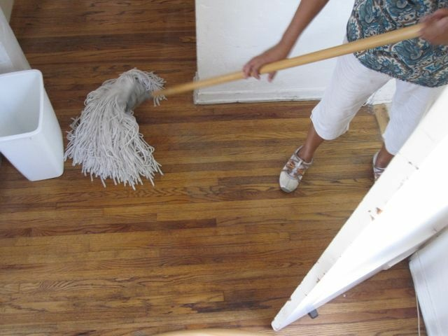 An undocumented housekeeper on her cleaning rounds, mopping a Los Angeles apartment, October 2010