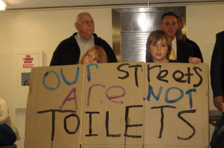 "Residents at Venice forum hold up ""Our Streets Are Not Toilets"" sign."