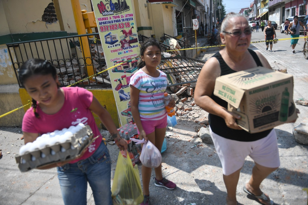 Local residents carry food on September 9, 2017 in Juchitan de Zaragoza after a powerful earthquake struck Mexico's Pacific coast.