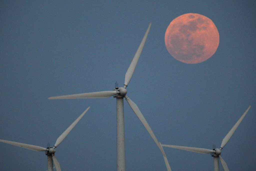 The moon rises behind wind turbines on May 5, 2012 near Palm Springs, California.