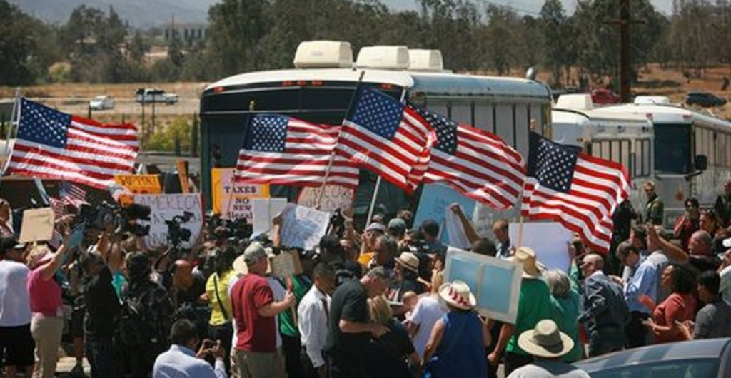 Protesters turn back three buses carrying 140 immigrants as they attempt to enter the Murrieta U.S. Border Patrol station for processing on July 1, 2014, in Murrieta, Calif.