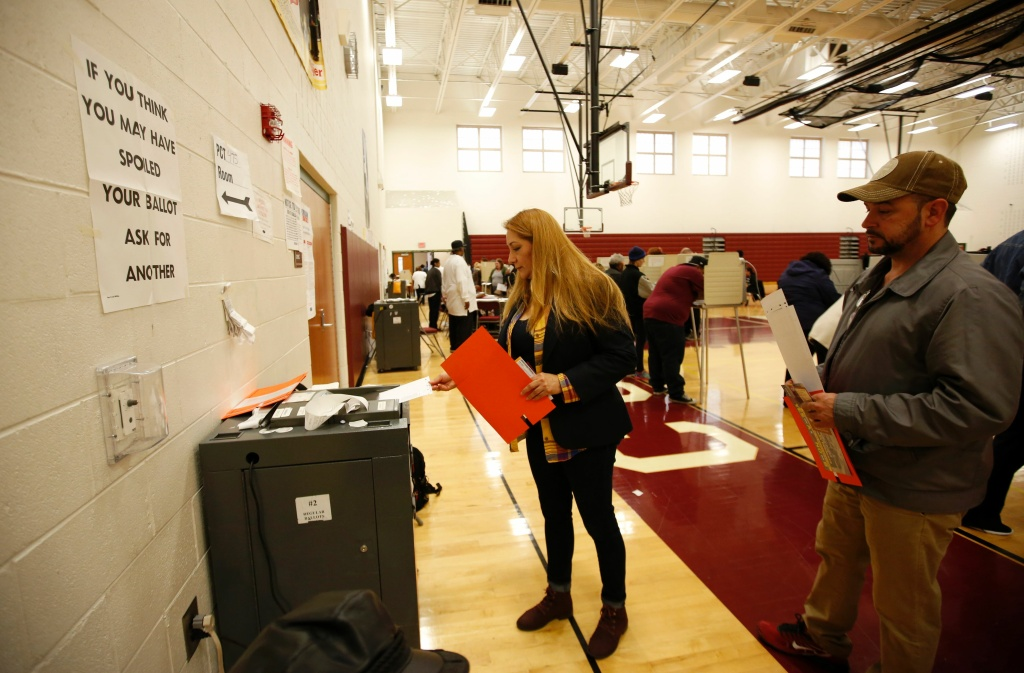 A woman places her ballot in the tabulation machine after voting at Western High School School in the U.S. presidential election on November 8, 2016 in Detroit, Michigan.
