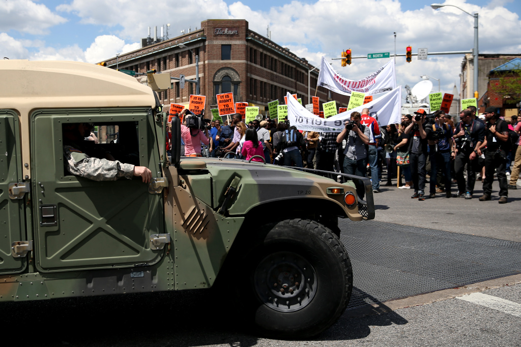 In this file photo, a National Guard truck drives by protesters in Baltimore, a day after authorities released a report on the death of Freddie Gray on May 2, 2015. The first of six police officers charged in the case went on trial Wednesday.