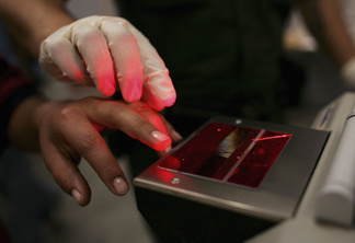 A woman gets her fingerprints taken after she was caught crossing the U.S. border with Mexico illegally, at the U.S. Border Patrol processing center June 21, 2006 in Nogales, Arizona.