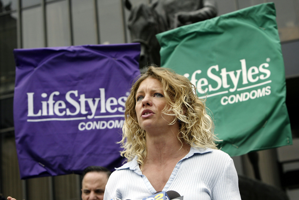 HIV-positive AIDS activist and former Playboy Bunny Rebekka Armstrong speaks to the press in front of banners that look like a giant condoms while calling on pornography executive, Larry Flynt, to voluntarily adopt a 100% condom use policy in his sexually explicit films, during a demonstration by the AIDS Healthcare Foundation outside the Flynt Publications building on June 7, 2004 in Los Angeles, California. That April, the $9-billion to $14-billion southern California adult film industry began a 30-day voluntary filming moratorium after two actors tested positive to HIV at the Adult Industry Medical Health Care Foundation (AIM) which tests the adult entertainers for HIV every 30 days. Last year a moratorium was called after a syphilis scare, and another was called this month when an actress tested positive for HIV. The latest moratorium was lifted Tuesday after all performers who worked with the actress were medically cleared.