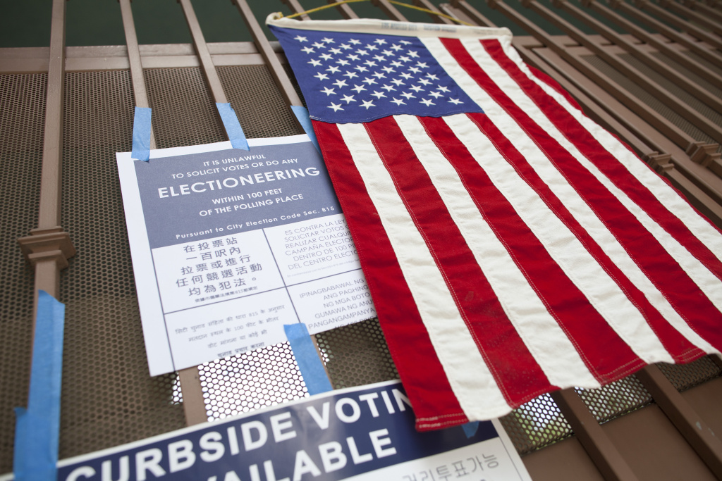 File photo. Election signs and a flag are posted on the gate at Angeles Mesa Elementary school during a special run-off election.
