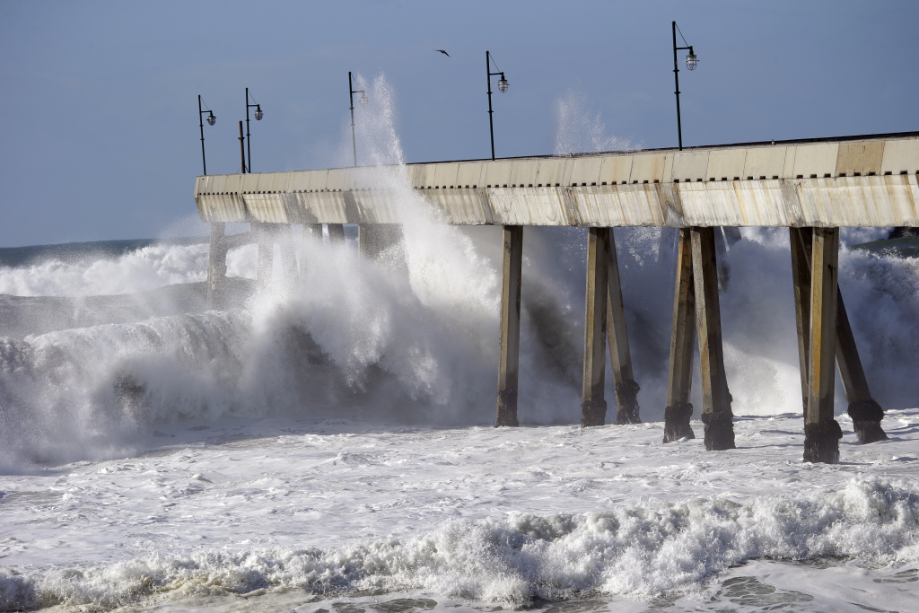 Waves crash on the municipal pier, Friday, Dec. 11, 2015, in Pacifica, Calif. The National Weather Service says the biggest storm of the season should quiet down in the Sierra Nevada before kicking back up Saturday. (AP Photo/Marcio Jose Sanchez)