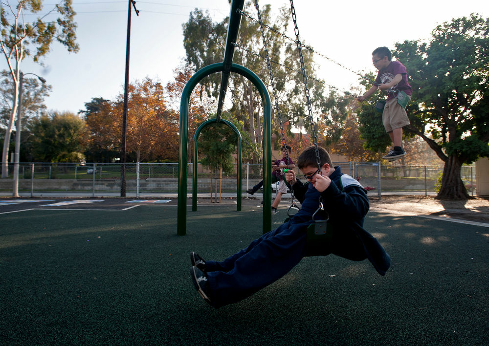 File photo. Fourth grader Daniel Fontes, center, enjoys a swing set that was part of a playground upgrade at Marguerita Elementary School. Voters approved the bond for the playground in 2008, and the bond was issued in 2010.
