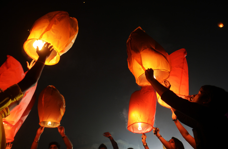 Indian volunteers of a social organization release sky lanterns to promote a peaceful and eco-friendly Diwali and create awareness against child labour in the fire cracker industry during a function in Kolkata on October 30, 2013. Diwali, the Festival of Lights, marks victory over evil and commemorates the time when Hindu god Lord Rama achieved victory over Ravana and returned to his kingdom Ayodhya.