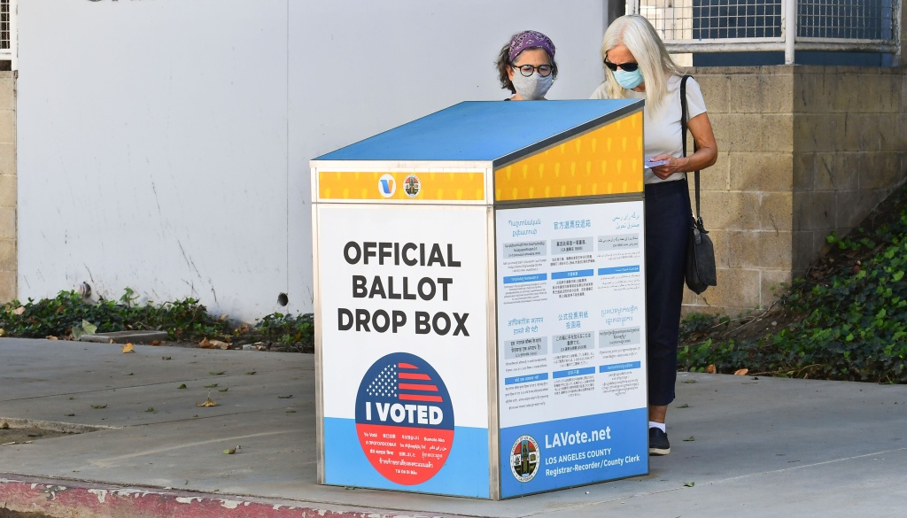 Voters cast their ballots for the 2020 US Elections at an offical ballot drop box on a sidewalk in Los Angeles, California on October 12, 2020, where election officials are looking into the use of unofficial ballot drop boxes installed by California's Republican Party. (Photo by Frederic J. BROWN / AFP) (Photo by FREDERIC J. BROWN/AFP via Getty Images)