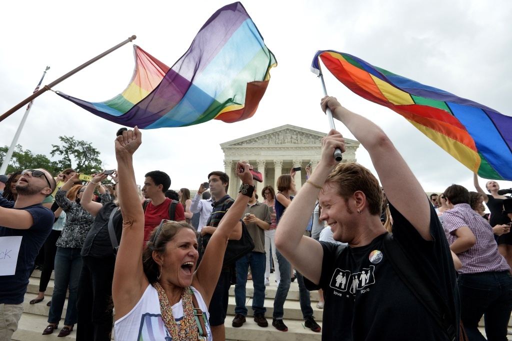People celebrate outside the Supreme Court in Washington, DC on June 26, 2015 after its historic decision on gay marriage. The US Supreme Court ruled Friday that gay marriage is a nationwide right, a landmark decision in one of the most keenly awaited announcements in decades and sparking scenes of jubilation. The nation's highest court, in a narrow 5-4 decision, said the US Constitution requires all states to carry out and recognize marriage between people of the same sex. AFP PHOTO/ MLADEN ANTONOV        (Photo credit should read MLADEN ANTONOV/AFP/Getty Images)
