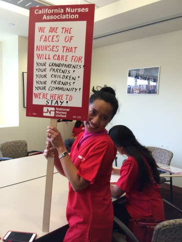 Roselle Gatdula has been a nurse at Kaiser Permanente's Los Angeles Medical Center for seven years. She writes on her picket sign for the nurses' strike that begins Tuesday.