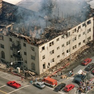 People and their belongings line a sidewalk across from a burned out apartment, 01 May 1992 in Los Angeles. The apartment was attached to a row of stores that were burned and looted, 30 April 1992. The 1992 Los Angeles riots, with looting and arson events, erupted 29 April 1992 when a mostly white jury acquitted the four police officers accused in the videotaped beating of black motorist Rodney King, after he fled from police. 52 people were killed during the riots and Rodney King became a reluctant symbol of police brutality.        (Photo credit should read HAL GARB/AFP/Getty Images)