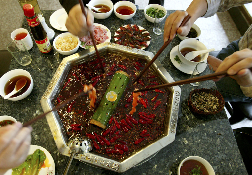 People share a hot pot at a restaurant in Chengdu, Sichuan Province, China on May 13, 2005.