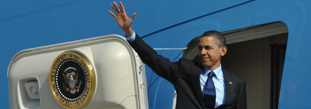 President Barack Obama makes his way aboard Air Force One.