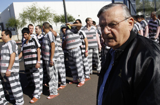 Inmates walk as they are moved after being ordered by Maricopa County Sheriff Officer Joe Arpaio (R), looking on, to be placed into new housing to open up new beds for maximum security inmates on April 17, 2009 in Phoenix, Arizona.