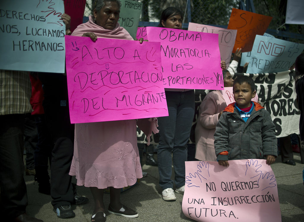 Mexicans members of migrants organizations hold signs during a protest in front of the US embassy against the trafficking of weapons to Mexico and the failure of the US immigration reform, on January 21, 2013, in Mexico City.