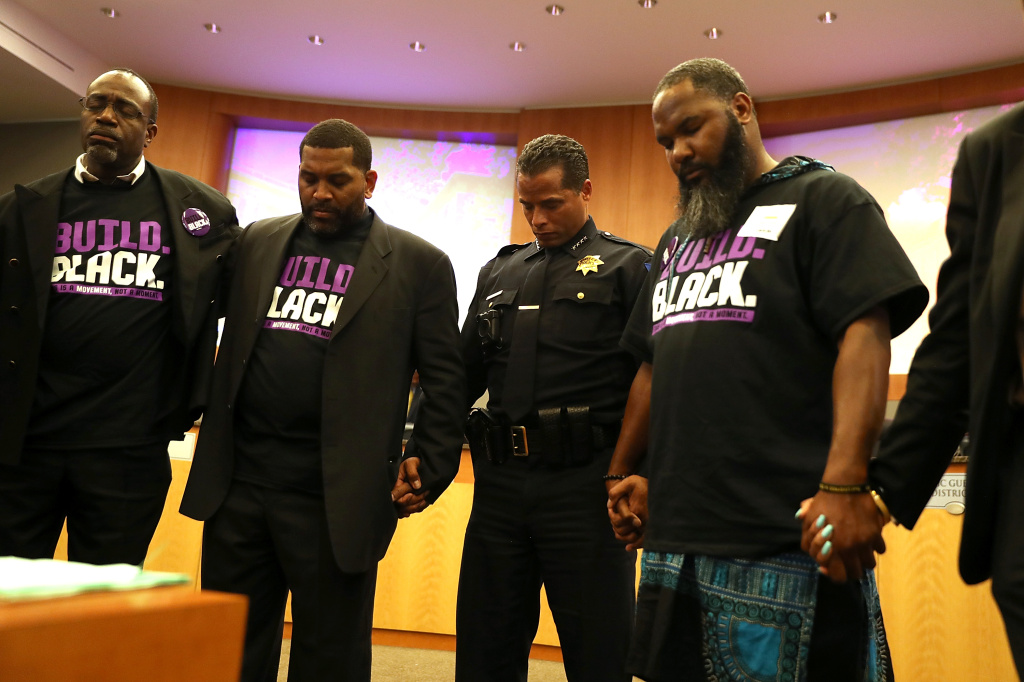 Sacramento police chief Daniel Hahn (C) prays after Stevante Clark, brother of Stephon Clark, disrupted a special city council meeting at Sacramento City Hall on March 27, 2018 in Sacramento, California.
