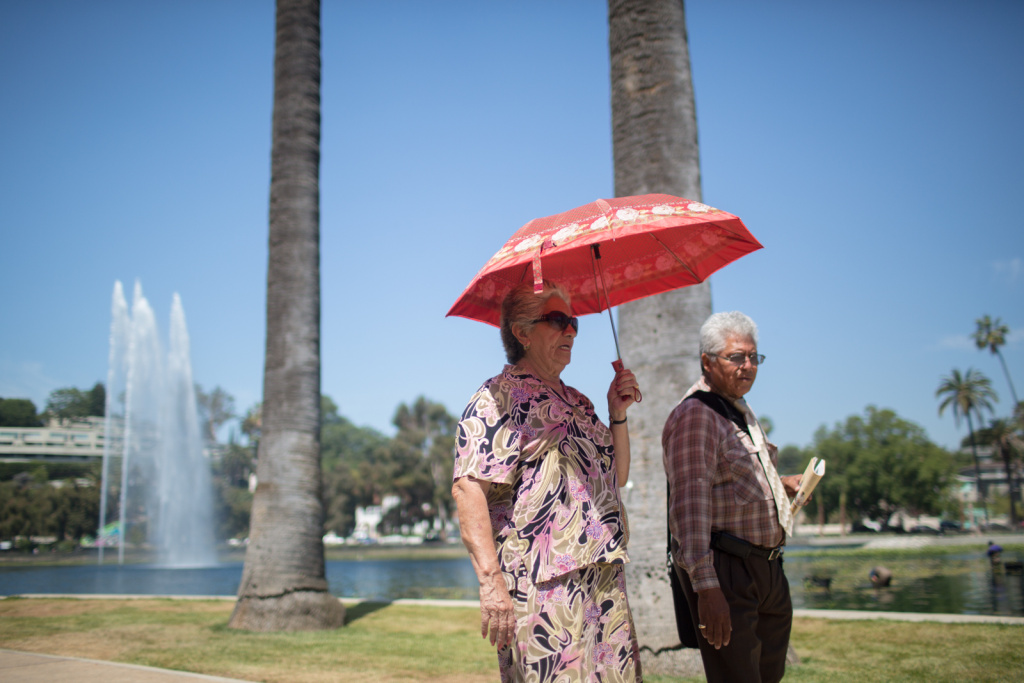 A man and woman walk around Echo Park Lake in this June 28, 2013, file photo. A winter heat wave is breaking December records in Southern California.