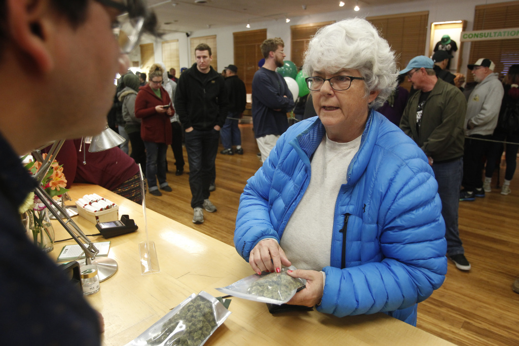 Margot Simpson, right, purchases marijuana at Harborside marijuana dispensary, Monday, Jan. 1, 2018, in Oakland, Calif. Starting New Year's Day, recreational marijuana can be sold legally in California.