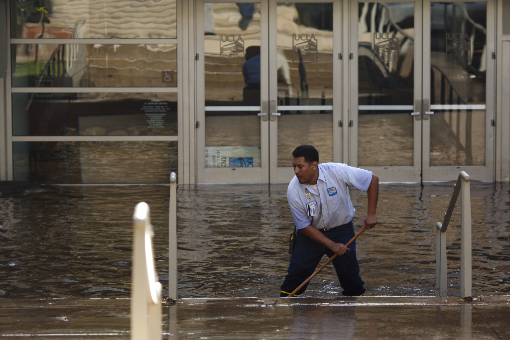 In file photo, a maintenance worker tires to mitigate flood damage to the UCLA campus after a water main broke on Sunset Boulevard.