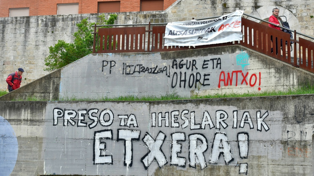 People in the Spanish Basque village of Agurain walk past graffiti calling for the return of ETA prisoners to the Basque country on Thursday. The Basque separatist group has formally announced its dissolution.