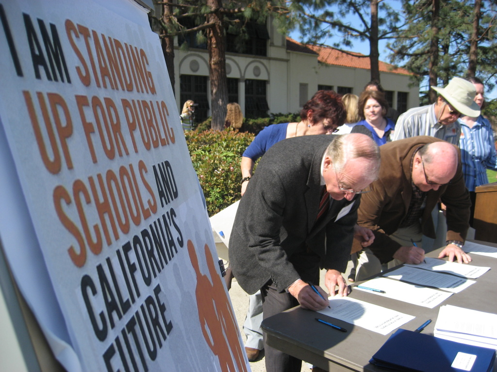 Torrance Unified School District parents, teachers and administrators line up to sign a petition against state education cuts outside of Torrance High School in Torrance, Calif.