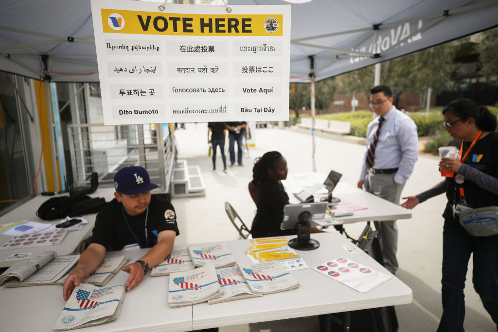 A voter (2nd R) checks in before entering a voting booth during early voting for the California presidential primary election at a new L.A. County 'Mobile Vote Center' in Grand Park in Los Angeles, California.