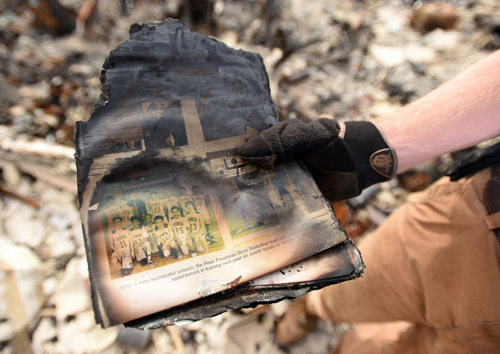 Ben Pedersen displays his partially burned high school yearbook that he found at his burned home in the Coffey Park area of Santa Rosa, California, on October 20, 2017. Residents are being allowed to return to their burned homes on October 20 to grieve and search through remains. Around 5,700 homes and businesses have been destroyed by the fires, the deadliest in California's history. / AFP PHOTO / JOSH EDELSON        (Photo credit should read JOSH EDELSON/AFP/Getty Images)