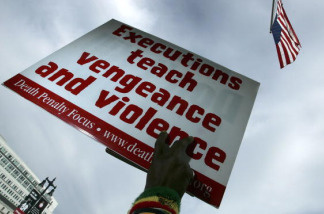 An opponent of the death penalty holds a sign during a rally.