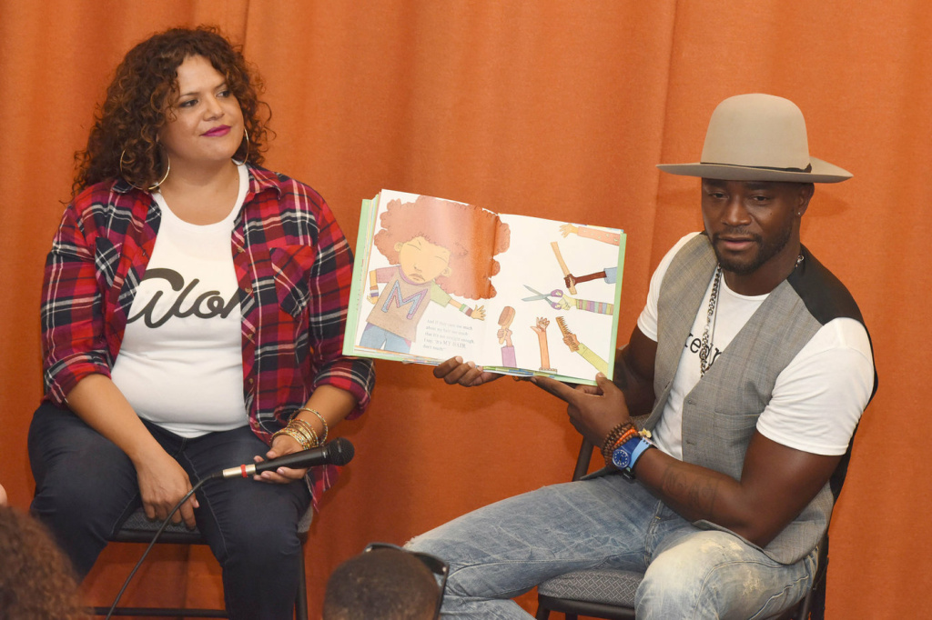 """Fashion designer Sonia Smith-Kang sits with actor Taye Diggs as he reads his book, """"Mixed Me,"""" to children in Los Angeles in 2015."""