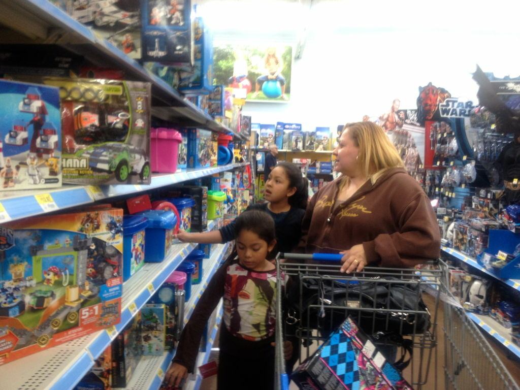 Hailey Mendoza, 7, and Jocelyn Mendoza, 9, shop with their mom Sandra Mejia at the Walmart in Rosemead. Mejia looking for gifts on Dec. 20, just five days before Christmas.