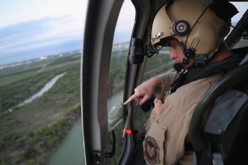 A U.S. Customs and Border Protection helicopter pilot searches for undocumented immigrants while flying a patrol over the U.S.-Mexico border on March 15, 2017 near La Grulla, Texas.
