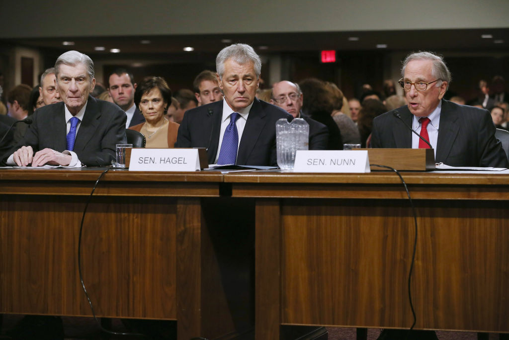 Former U.S. Sen. Chuck Hagel (R-NE) (center) listens to former U.S. Sen. John Warner (R-VA) (left) and former U.S. Sen. Sam Nunn (D-GA), both former chairmen of the Senate Armed Services Committee, as they deliver opening remarks during Hagel's confirmation hearing to become the next secretary of defense before the committee January 31, 2013 on Capitol Hill in Washington, DC.