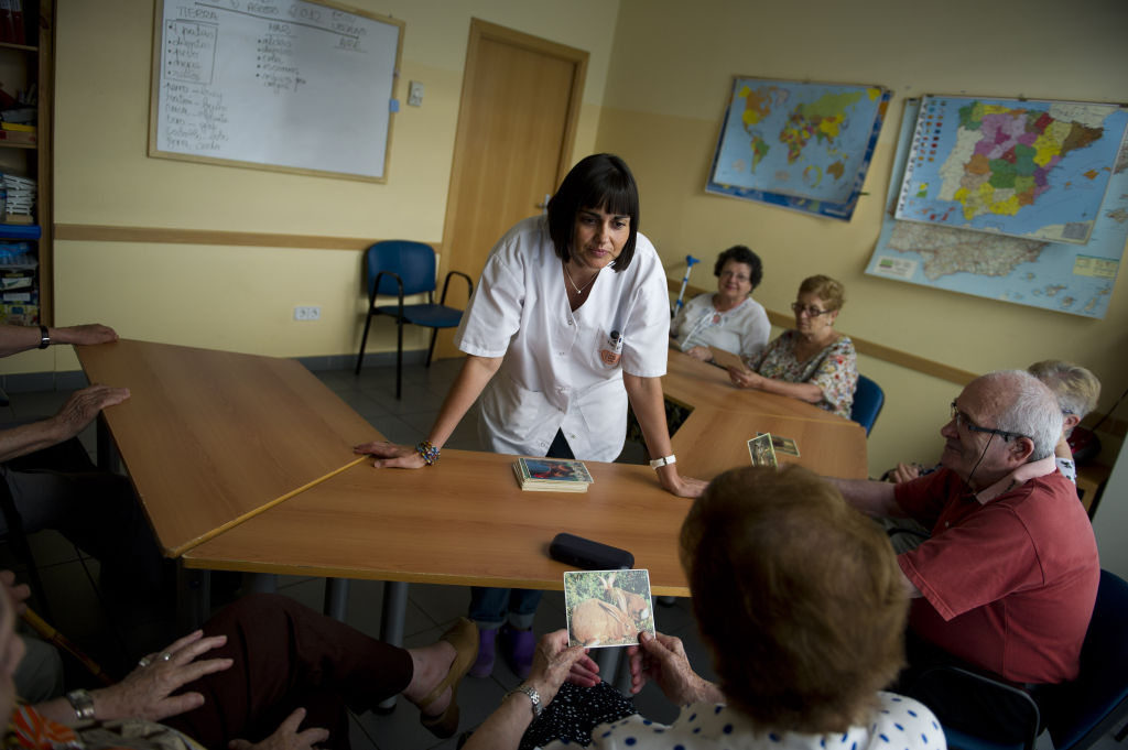 Social worker Virginia Sanchez helps elderly people during a memory activity at the Cuidem La Memoria elderly home , which specializes in Alzheimer patients on August 2, 2012 in Barcelona, Spain.