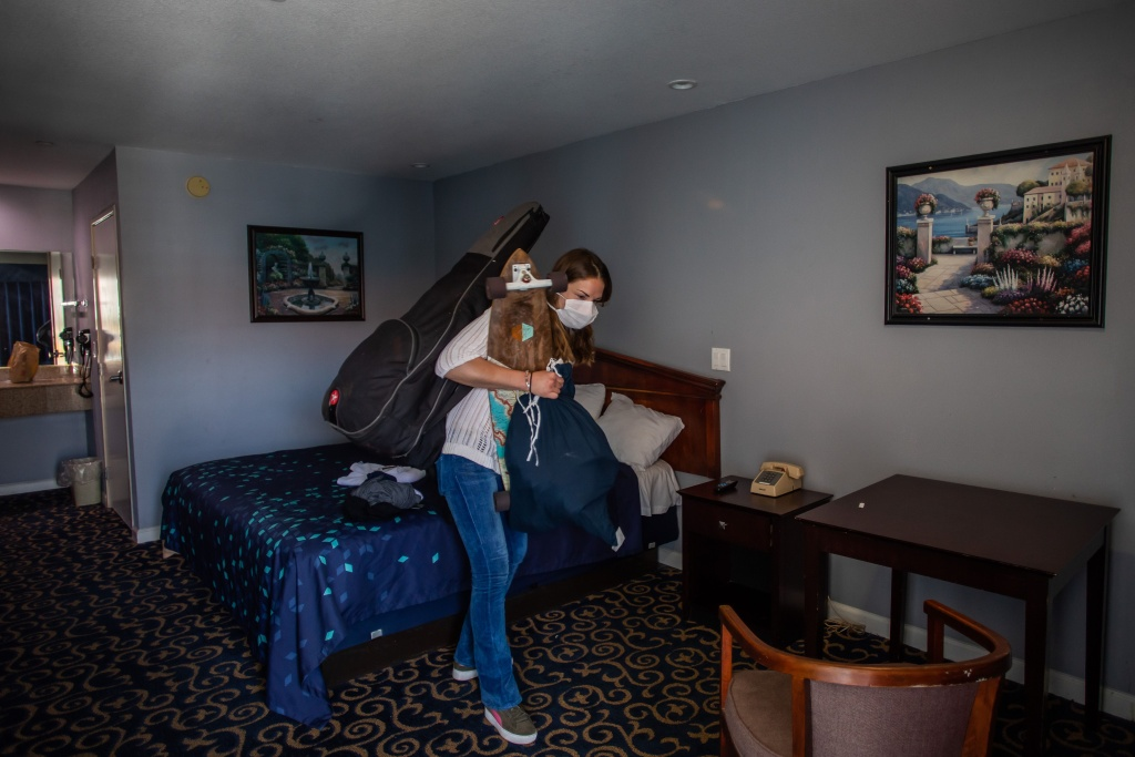 Julie Mariane gathers her belongings in a motel room provided to homeless people by the NGO St. Joseph Center, as she gets ready to be transferred to a hotel room in Venice Beach, California on April 26, 2020.