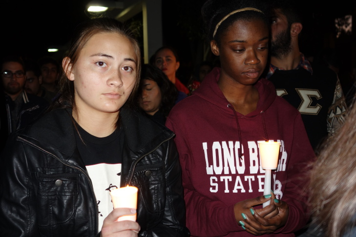 Freshmen Hannah Tsutsui, left, and Jordan Christian hold candles at a vigil for slain student Nohemi Gonzalez, who was killed in the Paris terror attacks Nov 13.