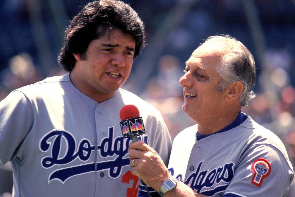Pitcher Fernando Valenzuela #34 of the Los Angeles Dodgers is interviewed by his manager Tommy Lasorda #2 before the game against the Chicago Cubs on June 7, 1981 at Wrigley Field in Chicago, Illinois.