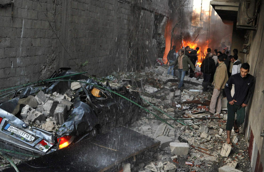 Syrian men inspect the scene of a car bomb explosion in Jaramana, a mainly Christian and Druze suburb of Damascus.
