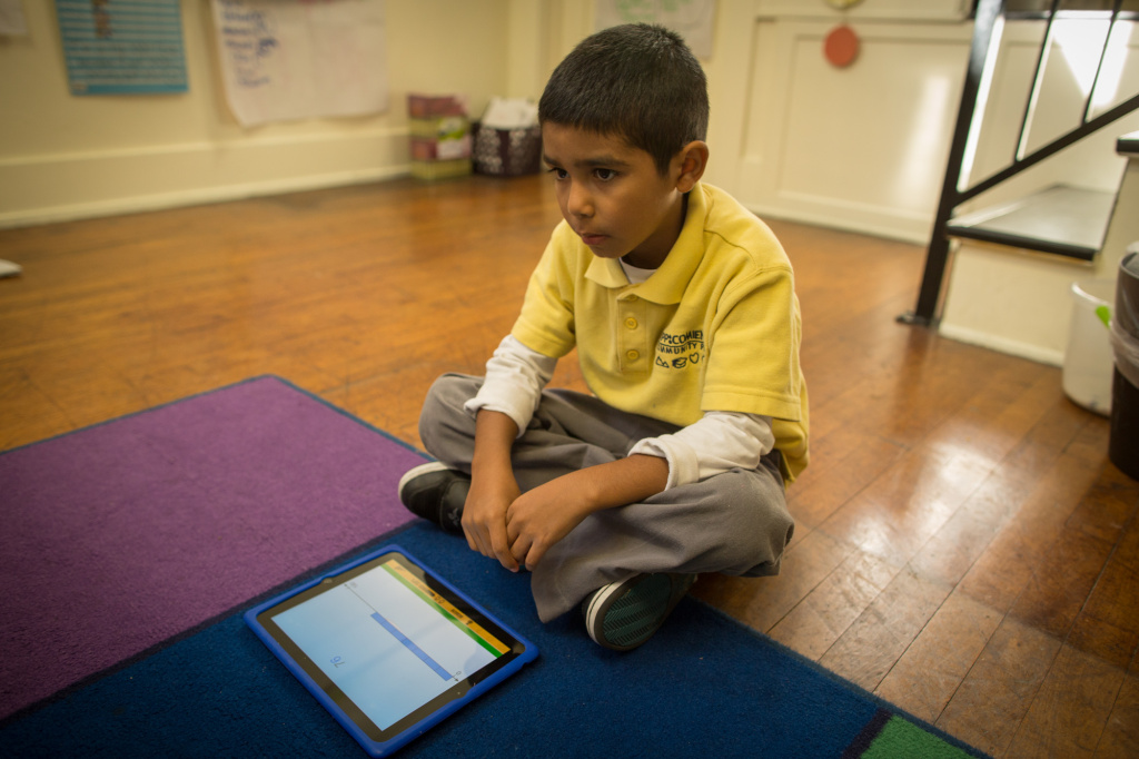Second grader Aiden C. listens to his teacher at the end of iPad instruction time at Comienza Community Prep in Huntington Park.