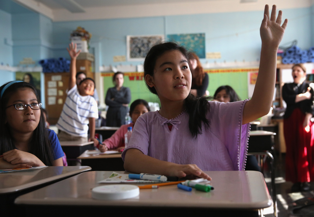 Tibetan immigrant children raise their hands during an after-school program for asylum immigrants run by the International Rescue Committee (IRC), on April 25, 2013 in the Queens borough of New York City.