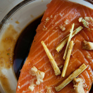 A slice of salmon with ginger, garlic and soy sauce sits in the coffee maker's carafe.